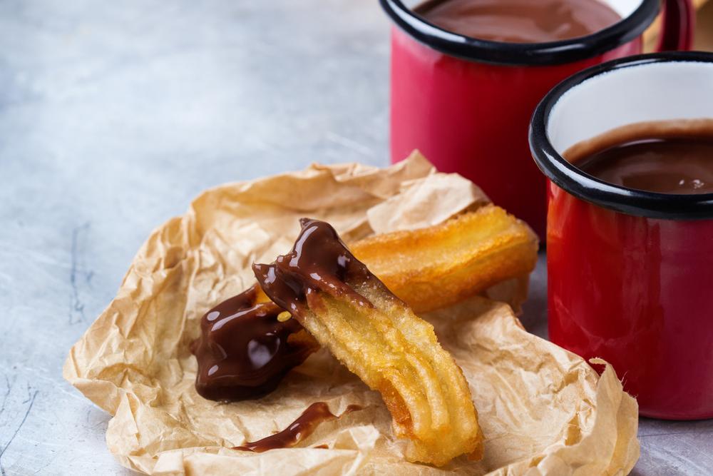 Traditional spanish churros with hot chocolate in a mug |©Antonina Vlasova/Shutterstock
