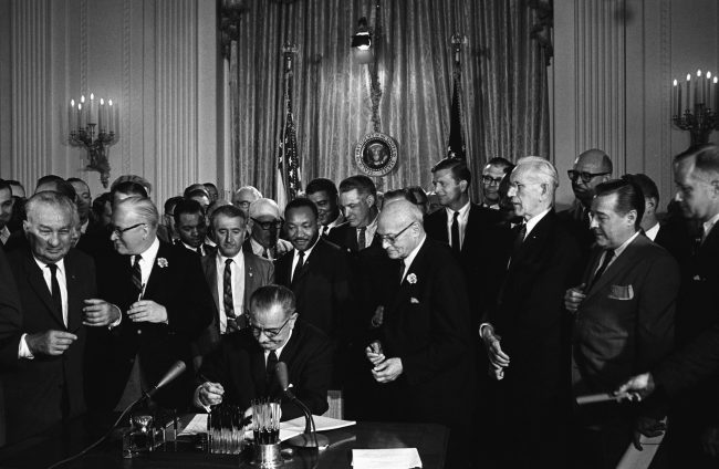 Lyndon Johnson signing the Civil Rights Act, 2 July 1964. Martin Luther king Jnr. looks on behind the President