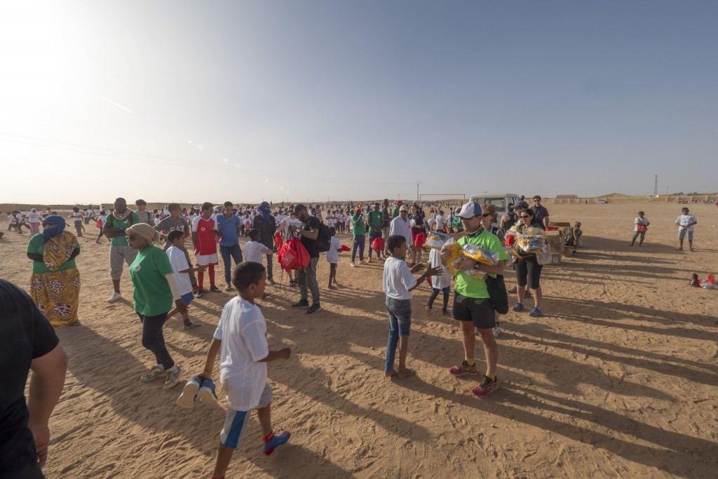 Volunteers handing bags and clothes to children after the 2017 Sahara Marathon | © Flickr/Sahara Marathon