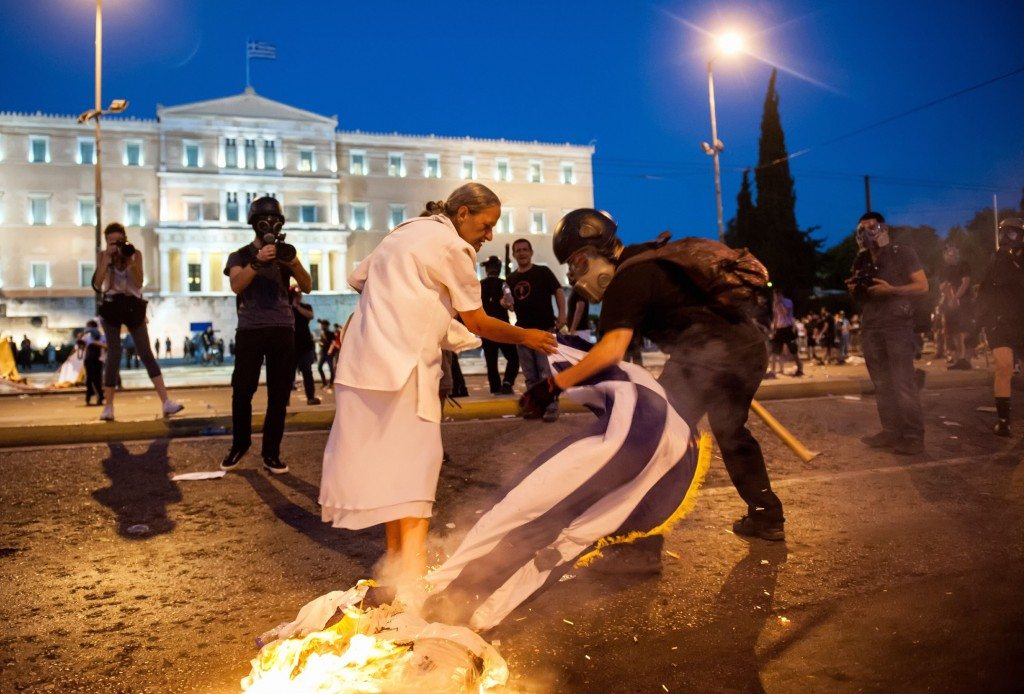 A woman attempts to stop a rioter from burning the Greek flag | © George Baboukos/Intime/Athen/REX/Shutterstock