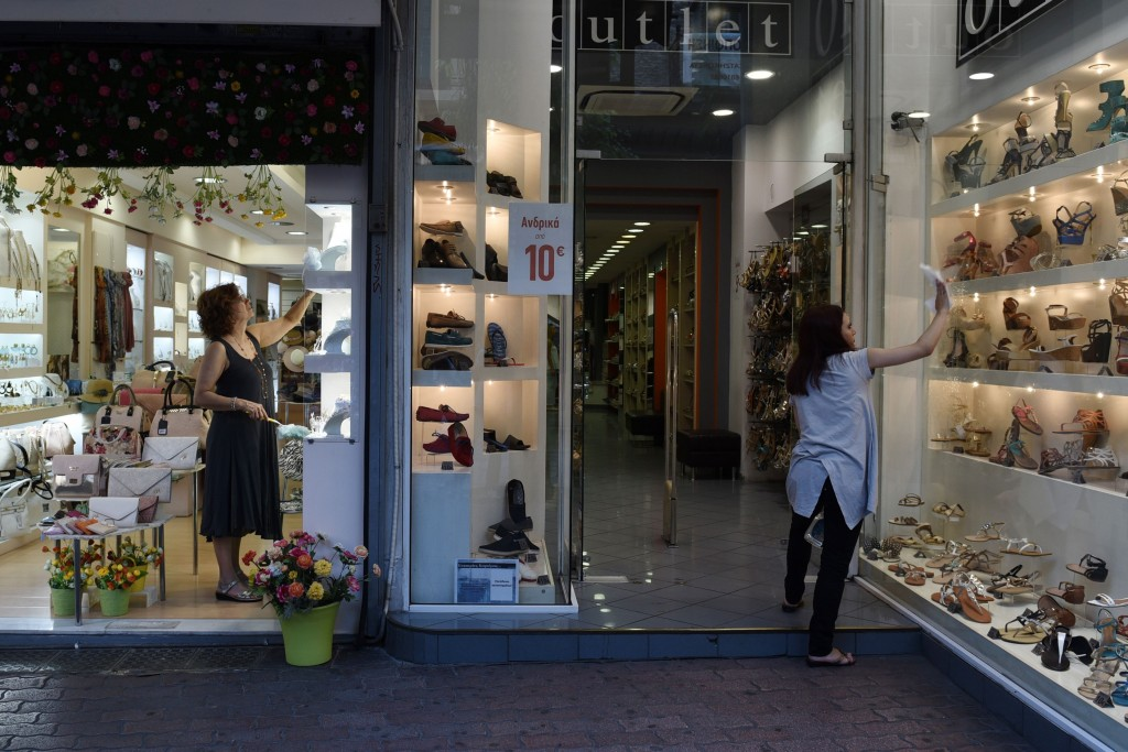 Two women clear the storefronts of their shops at Ermou Street, Athens | © Giannis Papanikos/AP/REX/Shutterstock